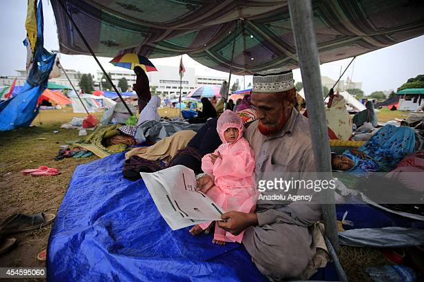 Pakistani antigovernment protestor reads a newspaper in a tent during his waiting at the parliament garden within the ongoing protests in Islamabad...