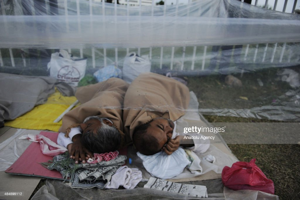 Pakistani anti-government protestors try to shelter from rain with plastic canvas during their waiting at the parliament garden within the ongoing protests in Islamabad, Pakistan on September 4, 2014. Supporters of Imran Khan, leader of Pakistan Tehreek-e-Insaaf (PTI), and Tahir-ul-Qadri, leader of Pakistan Awami Tehreek (PAT), keep their anti-government protests since August 14 demanding the resignation of the Prime Minister Nawaz Sharif at Islamabad's Red Zone where state buildings and parliament building are located.