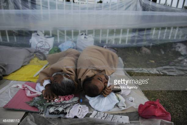 Pakistani antigovernment protestors try to shelter from rain with plastic canvas during their waiting at the parliament garden within the ongoing...