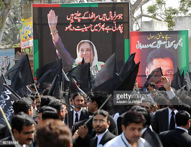 Pakistani antiMusharraf lawyers carry black flags as they gather in front of a huge poster of slain former premier Benazir Bhutto assassinated site...