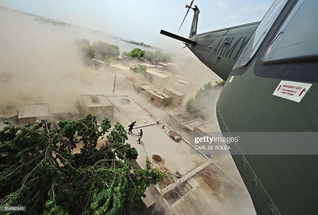 A Pakistani army helicopter churns up dust clouds as it drops aid on rooftops in Khairpur Nathan Shah town, which is surrounded by flood waters, in Sindh province, Pakistan, on September 14, 2010. A US official is quoted as saying the United Nations will raise an emergency appeal to support flood-ravaged Pakistan, despite concerns that an initial call to donors has fallen short. AFP PHOTO/Carl de Souza