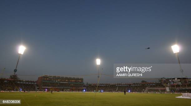 A Pakistani army helicopter flies past floodlights as it patrols prior to the start of the final cricket match of the Pakistan Super League with...