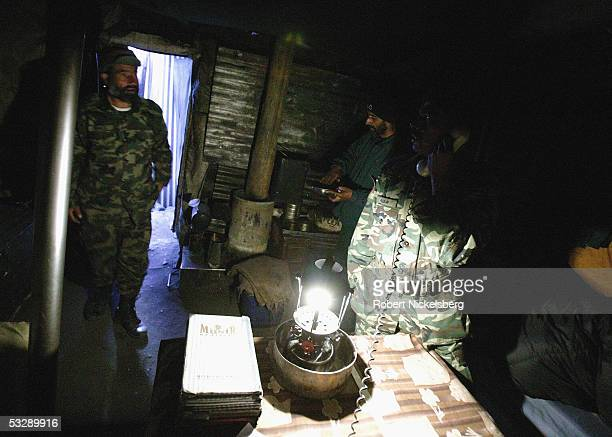 A Pakistani Army soldier answers a call while another cooks inside their barracks at 13800 feet June 17 2005 in Gyari Pakistan Since 198284 the...