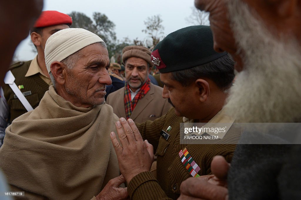 A Pakistani army soldier comforts with the father of a soldier who was shot dead along the Line of Control (LoC), at a village in Bainso, about 45 kms from the capital Islamabad, on February 16, 2013. Indian troops shot dead a Pakistani soldier along the de facto border in the disputed Kashmir region in the first deadly exchange since a truce was agreed a month ago, officials said Friday. AFP PHOTO/Farooq NAEEM