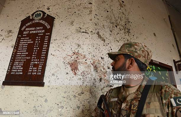A Pakistani army soldier looks at a plaque listing the best sports students at the site of the militants' attack on the armyrun school in Peshawar on...