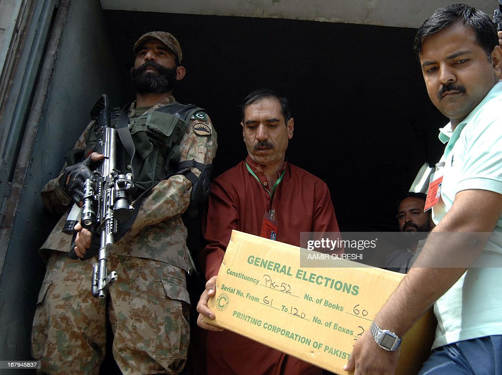 A Pakistani army soldier stands guard as election officials carry boxes containing electoral materials to be loaded onto a truck prior to its transporation for polling stations for the forthcoming parliamentary elections, in Islamabad on May 3, 2013. Pakistan will deploy more than 600,000 security personnel during next week's general election to guard against Taliban attacks that have marred campaigning. The May 11 polls will mark the first time that a civilian government has completed a full five-year term and handed over to an elected successor, in a country ruled by the military for half its 66-year history. AFP PHOTO/Aamir QURESHI