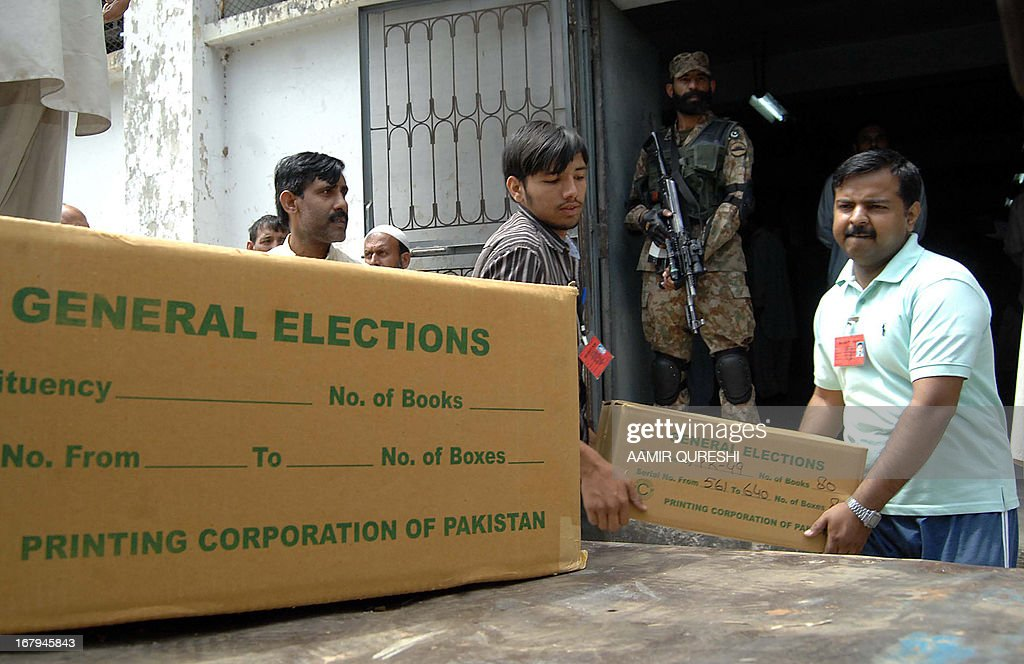 A Pakistani army soldier stands guard as election officials load electoral materials onto a truck prior to its transporation for polling stations for the forthcoming parliamentary elections, in Islamabad on May 3, 2013. Pakistan will deploy more than 600,000 security personnel during next week's general election to guard against Taliban attacks that have marred campaigning. The May 11 polls will mark the first time that a civilian government has completed a full five-year term and handed over to an elected successor, in a country ruled by the military for half its 66-year history. AFP PHOTO/Aamir QURESHI
