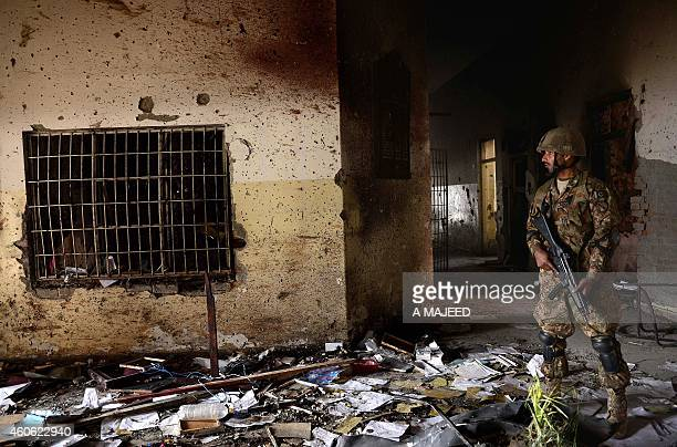 A Pakistani army soldier stands guard at the site of the militants' attack on the armyrun school in Peshawar on December 18 2014 Hundreds of students...