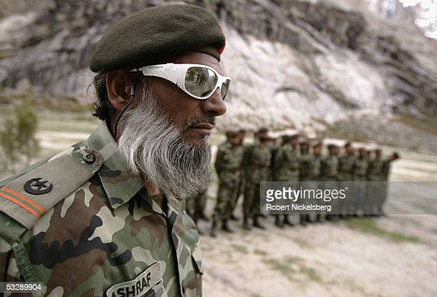 A Pakistani Army soldier wearing glacier glasses stands at attention to meet his unit's commanding officer during a training exercise near a...