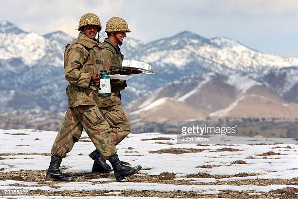 Pakistani Army soldiers carry tea to fellow troops at a military outpost near the border with Afghanistan February 17 2007 in the tribal area of...
