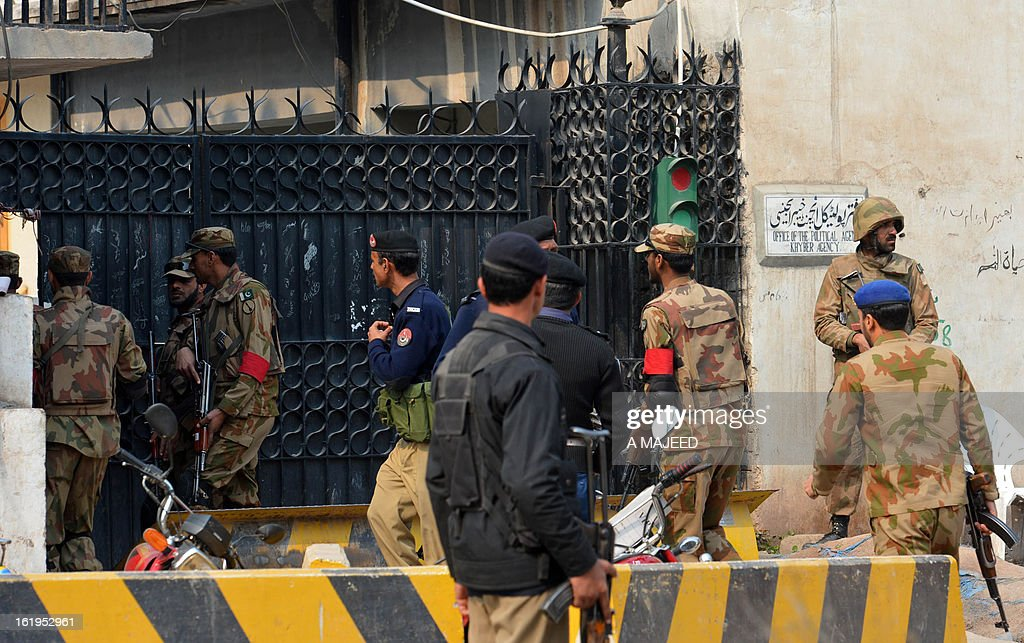 Pakistani army soldiers move at the office of the top political official of Khyber tribal region after the militants attack in Peshawar on February 18, 2013. Militants including a suicide bomber attacked the office of a senior official in Pakistan's northwestern city of Peshawar on Monday, killing five people, officials said. AFP HOTO/A MAJEED