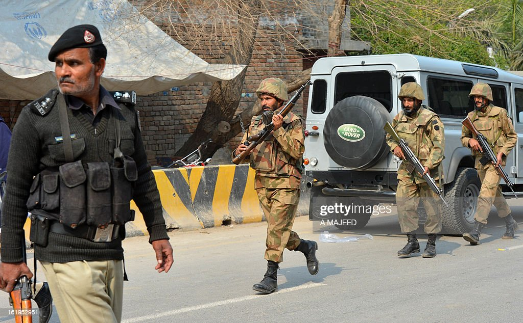 Pakistani army soldiers patrol outside the office of the top political official of Khyber tribal region after the militants attack in Peshawar on February 18, 2013. Militants including a suicide bomber attacked the office of a senior official in Pakistan's northwestern city of Peshawar on Monday, killing five people, officials said.