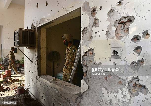 Pakistani army soldiers stand guard at the site of the militants' attack on the armyrun school in Peshawar on December 18 2014 Hundreds of students...