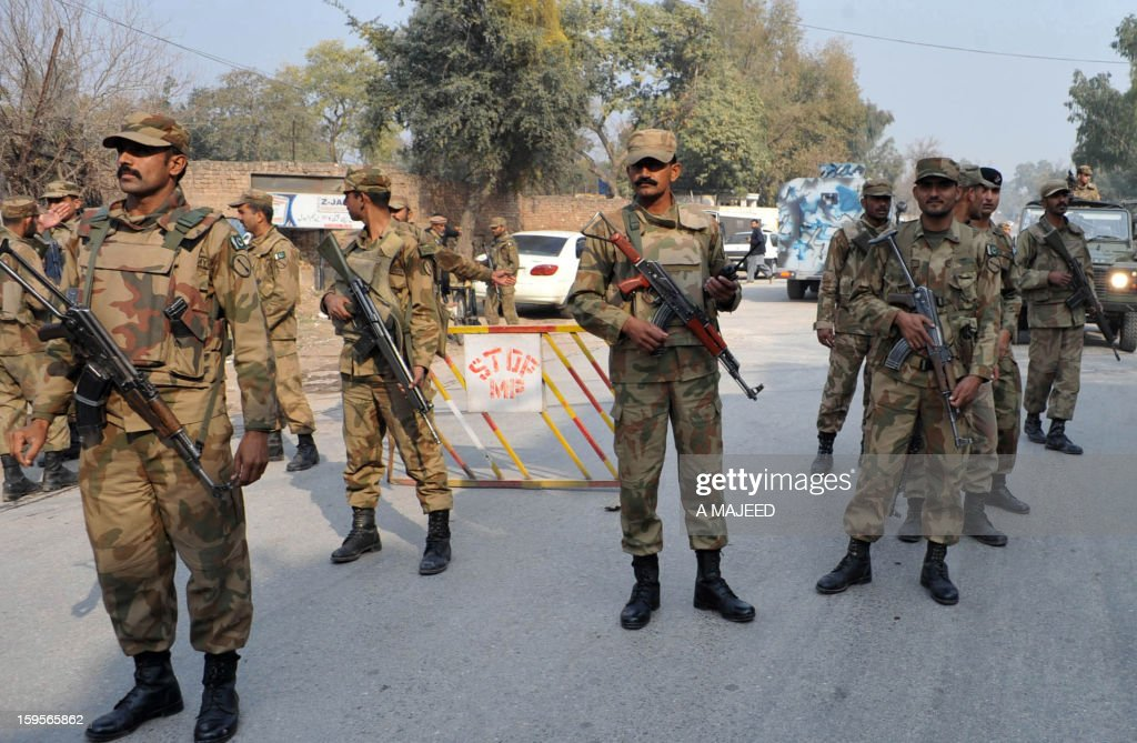 Pakistani army soldiers stand guard during a protest by villagers from the northwest in the provincial capital Peshawar on January 16, 2013. Demonstrators said gunmen wearing military uniforms stormed homes in Bara Tehsil in Khyber Agency, some 30 kilometers from Peshawar and shot 18 villagers dead in an overnight raid.