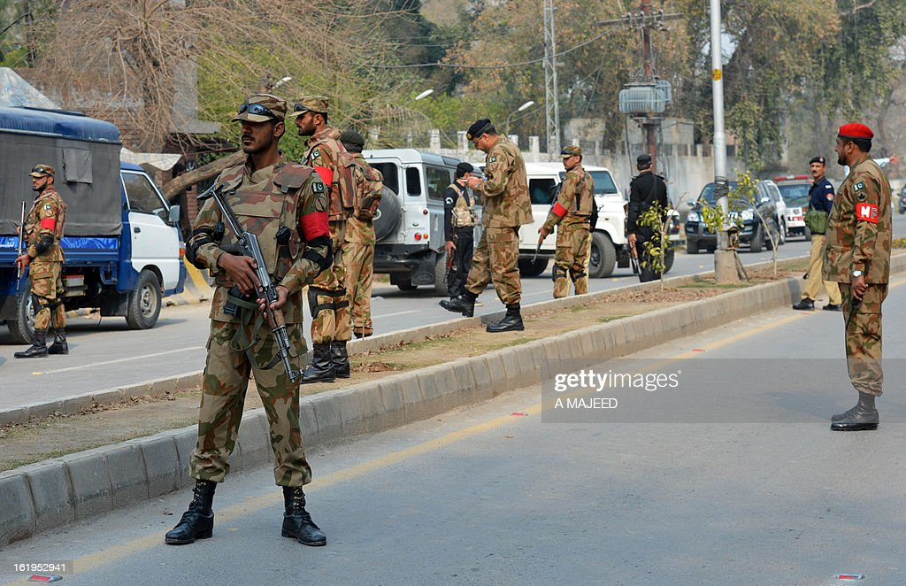 Pakistani army soldiers stand guard in front of the office of the top political official of Khyber tribal region after the militants attack in Peshawar on February 18, 2013. Militants including a suicide bomber attacked the office of a senior official in Pakistan's northwestern city of Peshawar on Monday, killing five people, officials said. AFP HOTO/A MAJEED