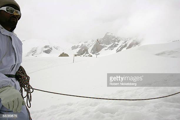 Pakistani Army soldiers walk down to their command center from a forward observation post using rope lines for safety on a spur of the Siachen...