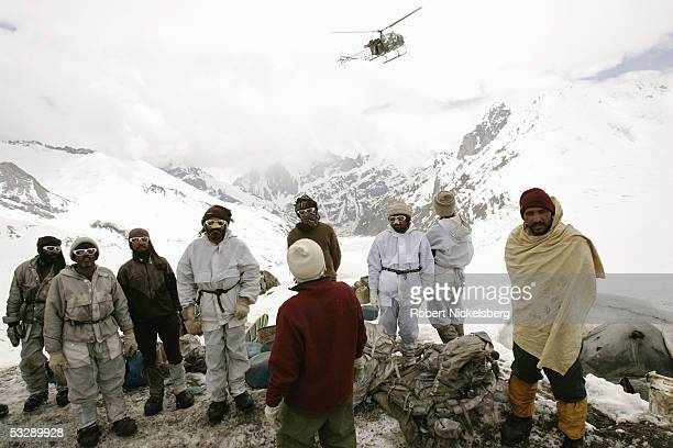 Pakistani Army soldiers watch as an Army helicopter hovers above their military outpost on a spur of the Siachen Glacier at 18655 feet June 19 2005...