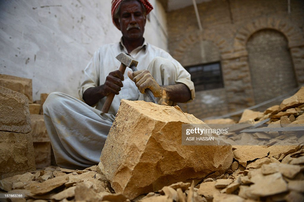 A Pakistani artisan chisels off pieces of mountain rock to form fancy bricks in Karachi on December 7, 2012. The community of artisans, who have been carving out fancy bricks for centuries, say their dying trade is facing existential threat due to the fragile economy in the South Asian nation, where high-end construction material can cost ten times more than regular cement bricks. AFP PHOTO/Asif HASSAN