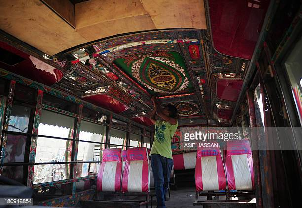 A Pakistani artisan works on a design on the interior of a passenger mini bus in Karachi on September 18 2013 Bus art has been very much in vogue in...