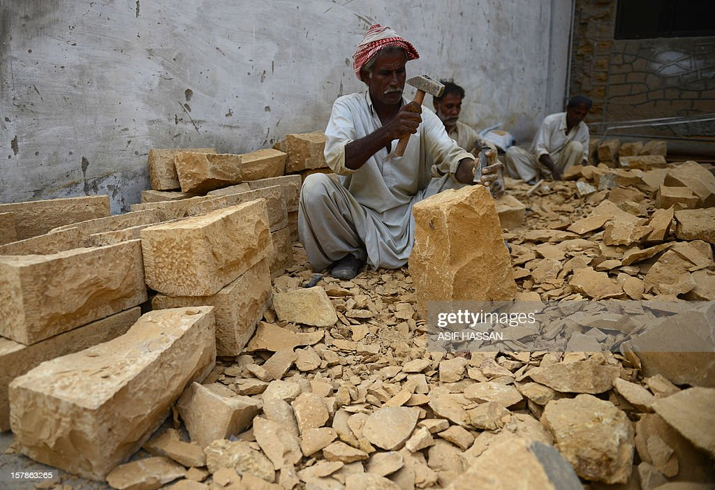 Pakistani artisans chisel off pieces of mountain rock to form fancy bricks in Karachi on December 7, 2012. The community of artisans, who have been carving out fancy bricks for centuries, say their dying trade is facing existential threat due to the fragile economy in the South Asian nation, where high-end construction material can cost ten times more than regular cement bricks. AFP PHOTO/Asif HASSAN