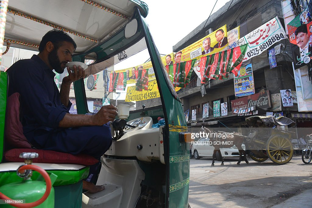 A Pakistani auto rickshaw driver sips Chai or tea on a street corner in the old city in Lahore on May 10, 2013, one day before some 86 million registered voters will go to the polls to elect lawmakers to the lower house of parliament and four provincial assemblies. Pakistan's general elections will mark the first democratic transition of power in the country's 66-year existence. AFP PHOTOS/Roberto SCHMIDT