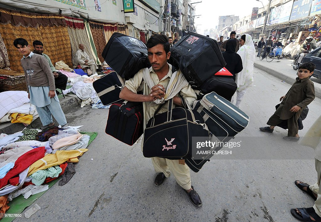 A Pakistani bag salesman walks through a market in Rawalpindi on March 4 2010 AFP PHOTO/ AAMIR QURESHI