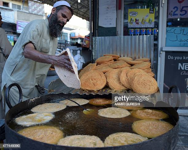 A Pakistani baker fries vermicelli to customers in preparation for the Muslim fasting month of Ramadan in Rawalpindi on June 17 2015 More than 15...