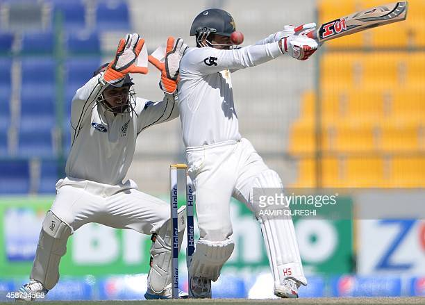 Pakistani batsman Ahmed Shahzad is hit on the helmet as he plays a shot while New Zealand wicketkeeper BJ Watling looks during the second day of the...