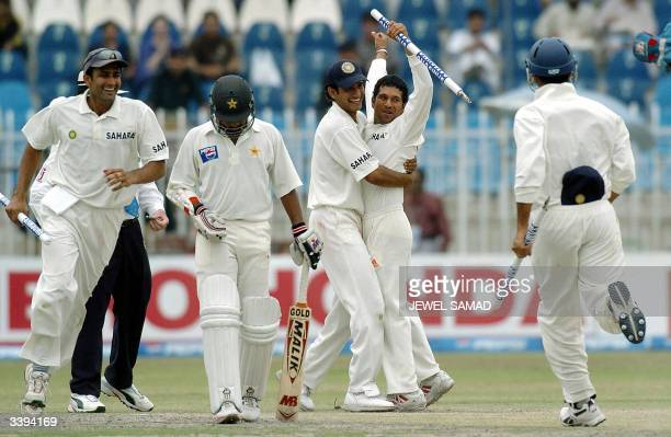 Pakistani batsman Asim Kamal keeps his head down as he passes by jubilant Indian cricketers Anil Kumble Sachin Tendulkar and Ashish Nehra after the...