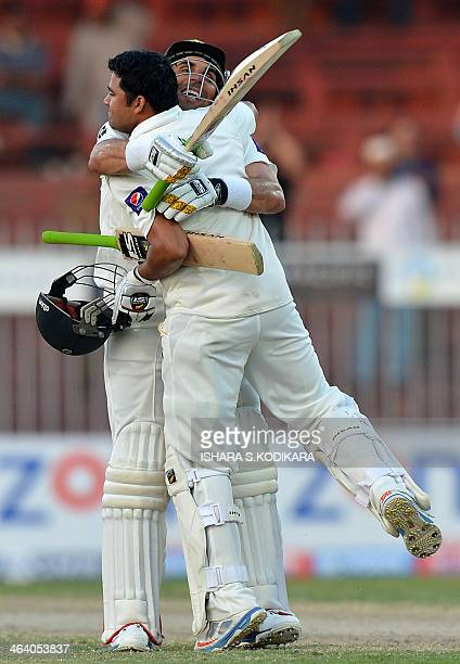 Pakistani batsman Azhar Ali celebrates after scoring a century with Pakistan's cricket team captain MisbahulHaq during the final day of their third...