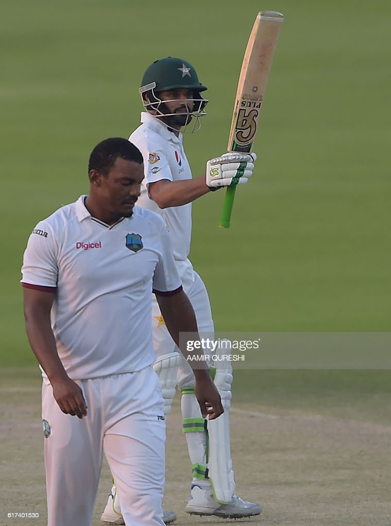 Pakistani batsman Azhar Ali (R) raises his bat after scoring 50 runs on the third day of the second Test between Pakistan and the West Indies at the Sheikh Zayed Cricket Stadium in Abu Dhabi on October 23, 2016. Openers Azhar Ali and Sami Aslam hit half-centuries to help Pakistan strenghten their grip on the third day of the second Test against West Indies in Abu Dhabi. Ali was batting on 52 and Asad Shafiq five not out to take Pakistan to 114-1, having an overall lead of 342 after dismissing West Indies for 224 in their first innings. / AFP / AAMIR