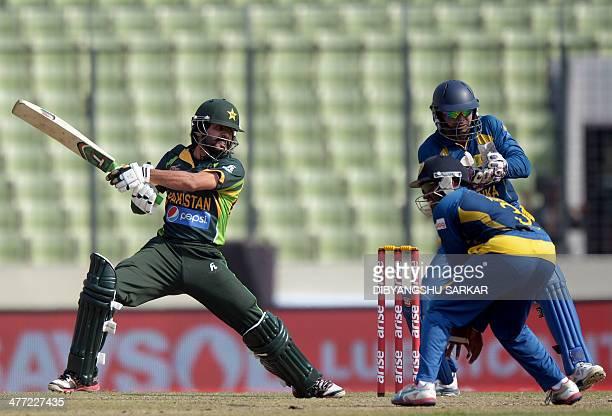 Pakistani batsman Fawad Alam plays a shot as Sri Lankan wicketkeeper Kumar Sangakkara and fielder Ashan Priy look on during the final match of the...