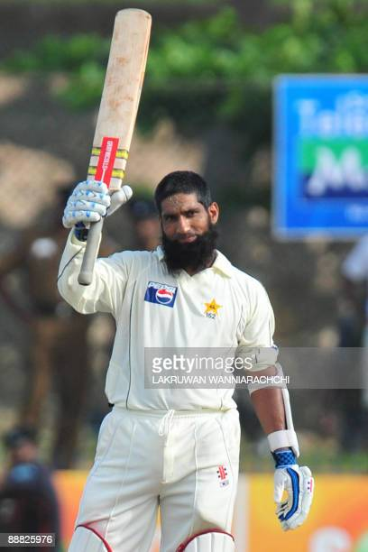 Pakistani batsman Mohammad Yousuf raises his bat in celebration after scoring a century during the second day of the first Test match between...