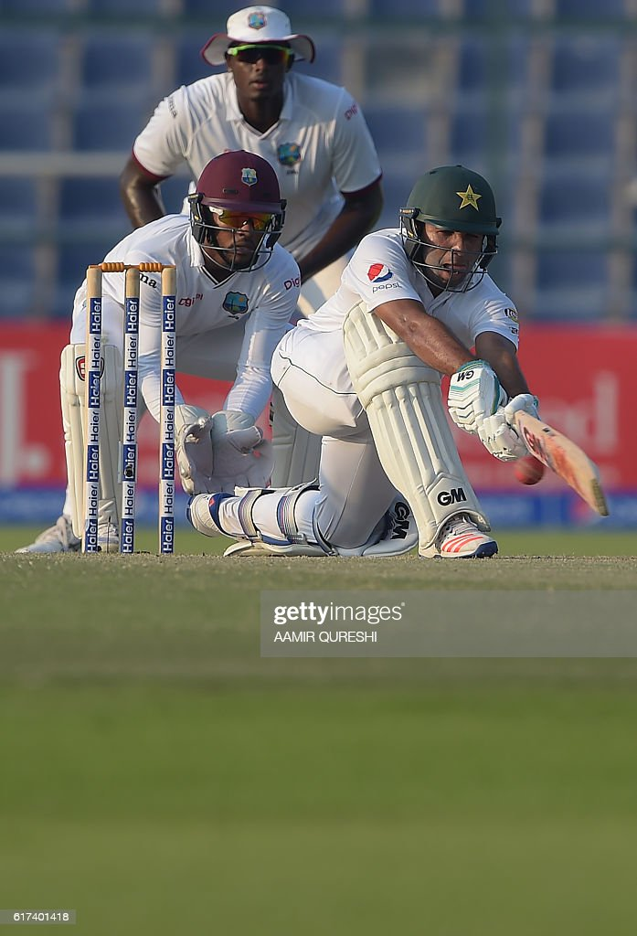 Pakistani batsman Sami Aslam (R) plays a shot as West Indies' wicketkeeper Shai Hope (L) looks on during the third day of the second Test between Pakistan and the West Indies at the Sheikh Zayed Cricket Stadium in Abu Dhabi on October 23, 2016. Openers Azhar Ali and Sami Aslam hit half-centuries to help Pakistan strenghten their grip on the third day of the second Test against West Indies in Abu Dhabi. Ali was batting on 52 and Asad Shafiq five not out to take Pakistan to 114-1, having an overall lead of 342 after dismissing West Indies for 224 in their first innings. / AFP / AAMIR