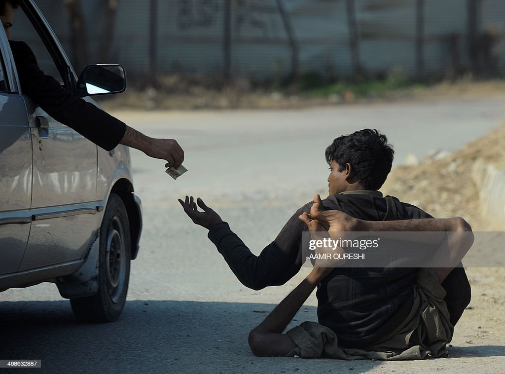 A Pakistani beggar who has been affected by polio receives money from a commuter on a street in Islamabad on February 11 2014 Pakistan is one of only...