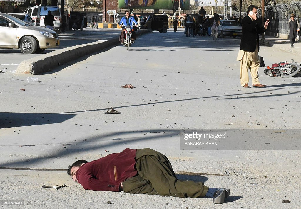 A Pakistani blast victim lays on a street after a bomb explosion that targeted a security convoy in Quetta on February 6, 2016. A bomb blast struck a paramilitary vehicle and killed at least eight people and wounded more than 35 others in southwestern Pakistani city of Quetta, official said. AFP PHOTO / BANARAS KHAN / AFP / BANARAS KHAN