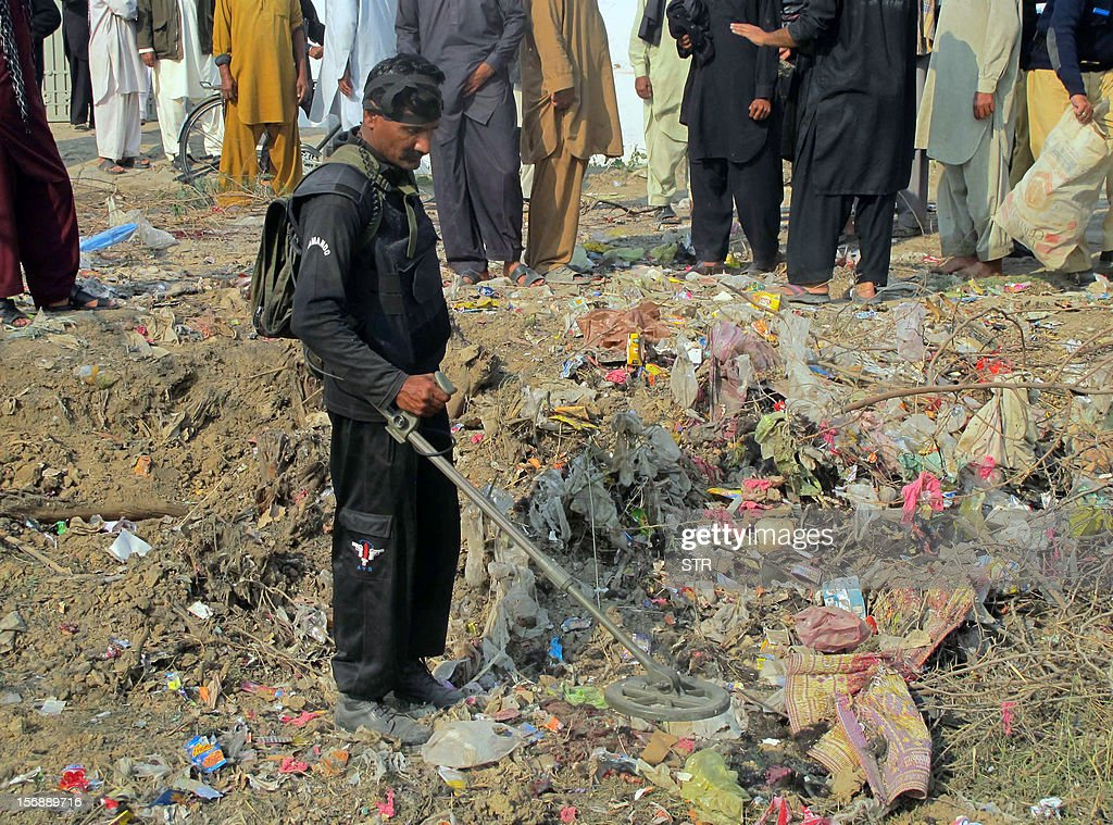 A Pakistani bomb disposal expert uses a metal detector at the site of a bomb explosion on the outskirts of Dera Ismail Khan in Khyber Pakhtunkhwa province on November 24, 2012. A bomb exploded near a Shiite religious procession in northwest Pakistan on November 24 killing seven people including four children, hospital officials said. The blast went off as people from the minority Shiite Muslim community were gathering to mark the anniversary of the death of the Prophet Mohammed's grandson Imam Hussain in 680.AFP PHOTO / STR