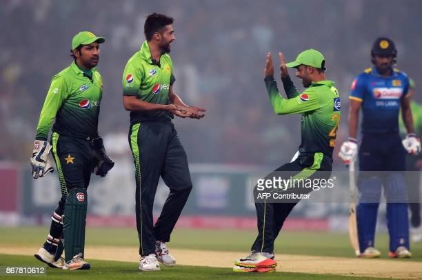 Pakistani bowler Mohammad Amir celebrates with teammates Shadab Khan and wicketkeeper Sarfraz Ahmad after dismissing Sri Lankan batsman Dilshan...