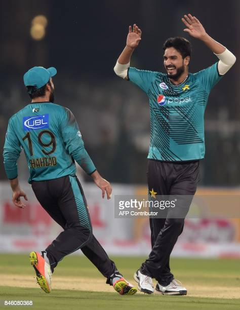 Pakistani bowler Rumman Raees celebrates with teammate Ahmed Shahzad after taking the wicket of World XI batsman Tamim Iqbal during the first...