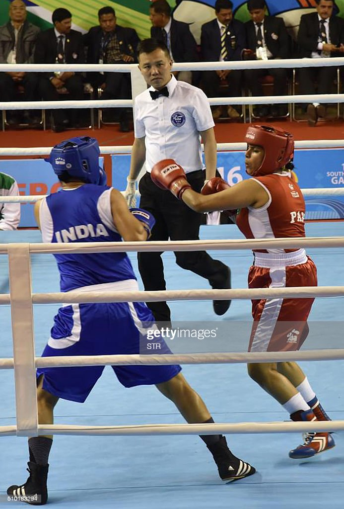 Pakistani boxer Javed Sofiya (R) competes against Indias Pooja Rani during a boxing match at the 12th South Asian Games 2016 in Shillong on February 14, 2016. Three Pakistani women are making history this weekend as they step into the boxing ring at the South Asian Games in India, the first time the conservative Muslim nation has fielded women boxers internationally. Khoushleem Bano, Rukhsana Parveen and Sofia Javed say to achieve their dream of competing they had to battle conservative groups in Pakistan who believe women should not participate in the sport. AFP PHOTO / STR / AFP / STR