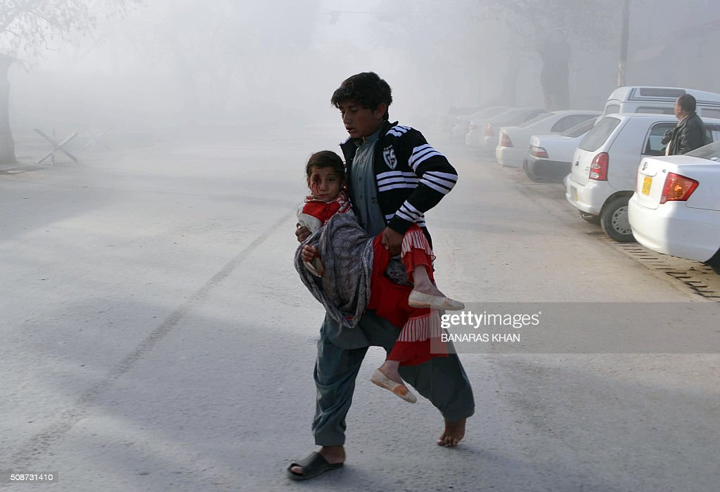 A Pakistani boy carries an injured girl from the site of a bomb explosion that targeted a security convoy in Quetta on February 6, 2016. A bomb blast struck a paramilitary vehicle and killed at least eight people and wounded more than 35 others in southwestern Pakistani city of Quetta, official said. AFP PHOTO / BANARAS KHAN / AFP / BANARAS KHAN