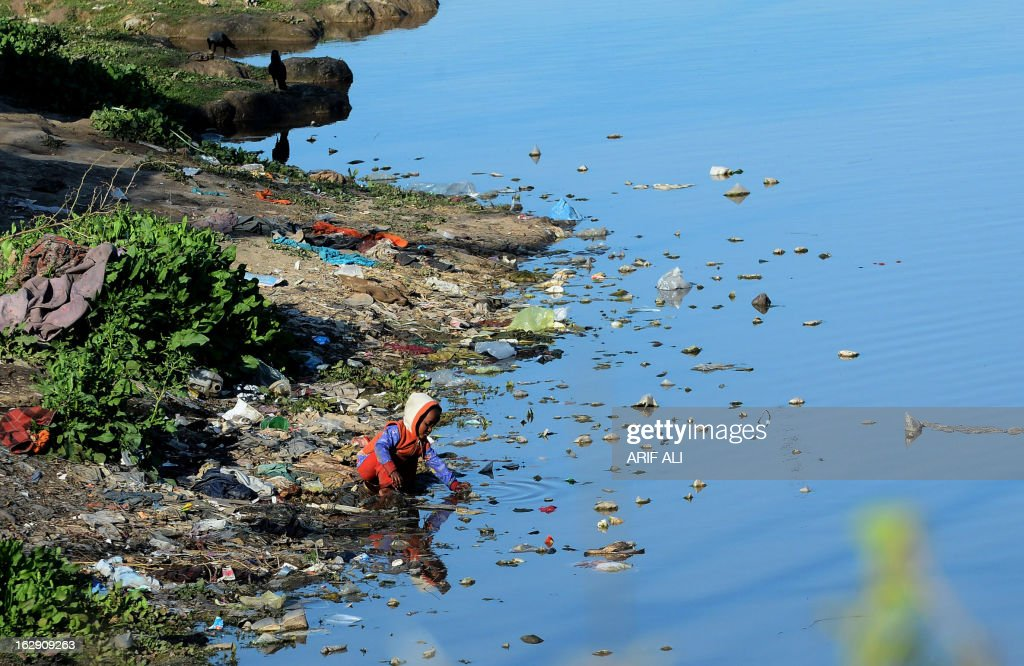 A Pakistani boy plays in the waters of a polluted canal in Lahore on March 1, 2013. AFP PHOTO/Arif ALI