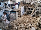 A Pakistani boy stands on the rubble of houses after an earthquake in Kohat on October 26 2015 A powerful 75 magnitude earthquake killed at least 70...