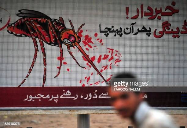A Pakistani boy walks past the awareness advertisement against the deadly tropical disease dengue fever in Islamabad on September 30 2011 In less...
