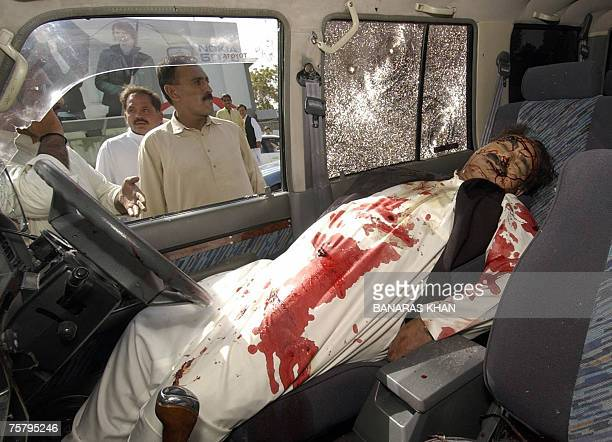 Pakistani bystanders look at the body of Baluchistan provincial spokesman Raziq Bugti as it lies in a vehicle after gunmen shot him dead in Quetta 27...
