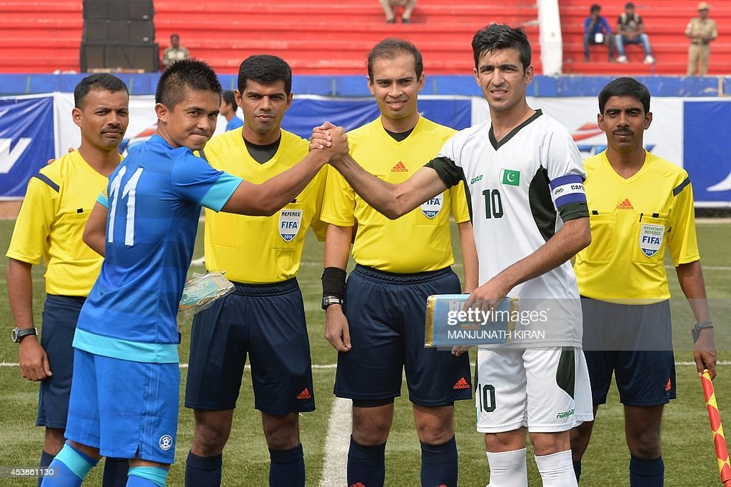 Pakistani captain Kaleem Ullah (2R) and his Indian counterpart Sunil Chhetri (2L) shake hands before the start of their second friendly football match in Bangalore at the Karnataka State Football Association Stadium in Bangalore on August 20, 2014. Pakistan pulled off a surprise 2-0 win over India, with a late goal from Saddam Hussain ensuring a share of the spoils for the visitors in the first football series between the arch rivals for a decade. AFP PHOTO/Manjunath KIRAN