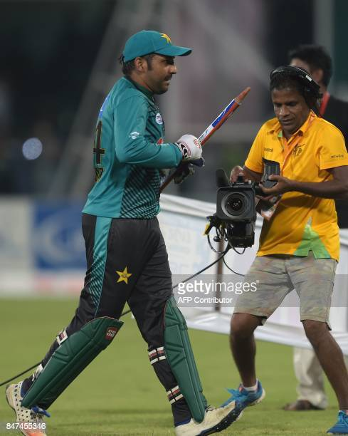 Pakistani captain Sarfraz Ahmad holds a wicket as walks back to pavilion after winning the third and final Twenty20 International match against World...