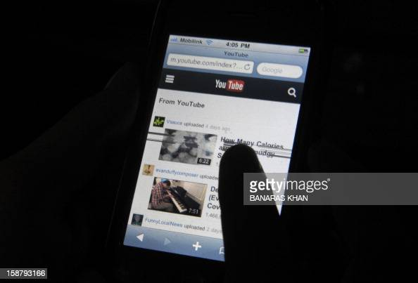 A Pakistani cell phone user browses YouTube on his mobile phone in Quetta on December 29 2012 Pakistan briefly unblocked access to the popular video...
