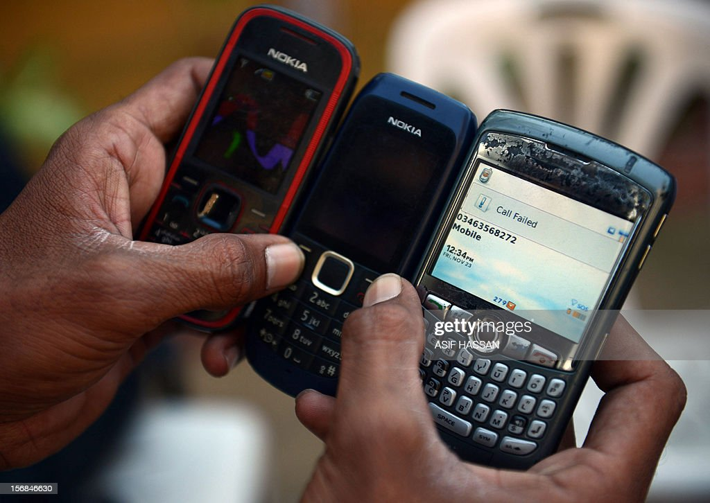 A Pakistani cellular phone user poses with his instruments having failed to make a call following the suspension of mobile phone services in Karachi on November 23, 2012. Pakistan suspended mobile phone services in major cities to prevent terror attacks from marring commemorations for the holy month of Muharram, officials said. AFP PHOTO/Asif HASSAN