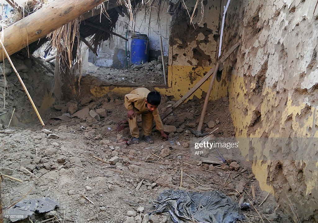 A Pakistani child sifts through rubble at a destroyed religious seminary belonging to the Haqqani network after a US drone strike in the Hangu...